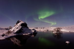 Beauty of nature in landscapes is seen in this view of aurora borealis reflecting on a lake