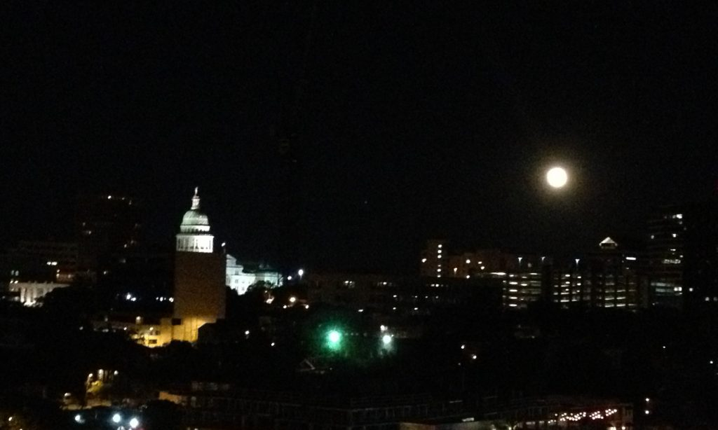 A full moon glows and state capital shines over downtown Austin, Texas
